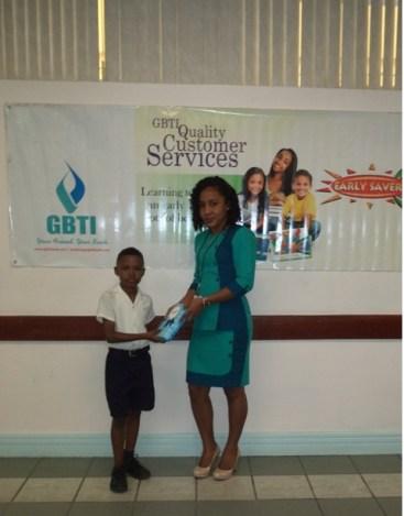 Jaden Persaud receives his prize from GBTI Regent Street Staff Ms Noelle Jeffrey.