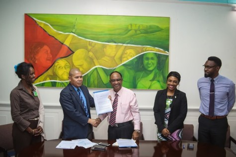 Minister of Social Cohesion, Dr. George Norton receiving the agreement from Guyana Amazon Warriors Operation Manager, Omar Khan in the presence of Director of Sport, Christopher Jones, Assistant Director of Sport, Melissa Dow-Richardson and Permanent Secretary to the Ministry, Melissa Tucker.