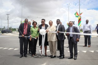 Minister within the Ministry of Public Infrastructure, Annette Ferguson surrounded by Minister of Public Infrastructure, David Patterson (front left) and Prime Minister, Moses Nagamootoo (third right) as she cuts the ribbon to officially open the roundabout.