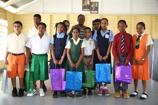 Minister Henry poses with the top 10 performers of Region Five