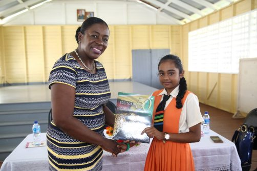 Top performer of Region Five Anne Khemraj receives a copy of Guyana at 50 from Minister Nicolette Henry