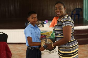 Top performer for Region Six Ranjiv Babulall receives a copy of Guyana at 50 from Minister Nicolette Henry