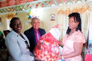 Minister of Education, Hon. Nicolette Henry and Minister of Social Cohesion, Hon. Dr. George Norton handing over some of the supplies to Beyonce Ross' mother.