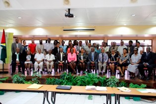 Participants of the consultation exercise pose for a photo-opportunity with the Minister of Education, Hon. Nicolette Henry (seated eighth from right) and Vice-Chancellor of UG, Professor Ivelaw Griffith, (seated fifth from left).