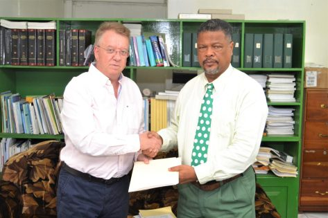Oldendorff Carriers Guyana Inc GM Ulf Henriksson handing over employee information to Chief Labour Officer Charles Ogle