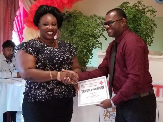 Senior Occupational Safety and Health Officer, Neville Nichols handing over a certificate to a graduant