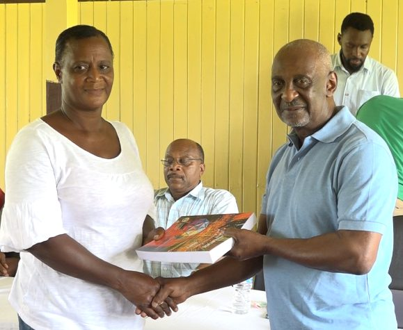 Minister within the Ministry of Social Protection, Keith Scott hands over a book to one of the Baracara residents