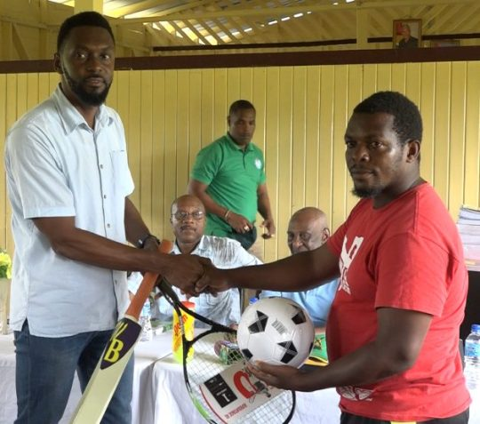 Director of Sport, Christopher Jones hands over sporting gear to one of the Baracara residents
