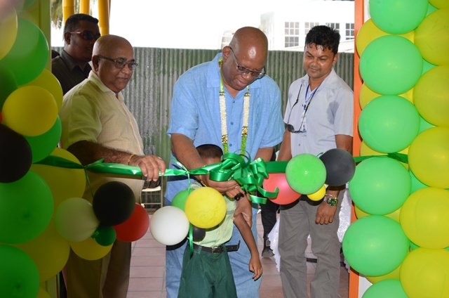 (left to right) Regional Executive Officer (REO) Denis Jaikaran Minister of Finance Winston Jordan and a BNTF representative cut the ribbon for the official commissioning of the Anna Catherina Early Childhood Development centre