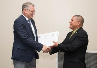 Head of the European Union Delegation, Ambassador Jernej Videtic presenting a copy of the plan to Minister of Social Cohesion with responsibility for Culture, Youth and Sport, Dr. George Norton.