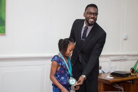 Director of Sport, Christopher Jones decorating Somayia Orna with a medal from the National Sports Commission.