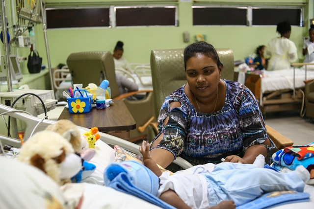 Bibi Shareema Haleem, mother of one of the babies who underwent heart surgery, tends to her baby boy as he responds to recovery treatment at the Georgetown Public Hospital