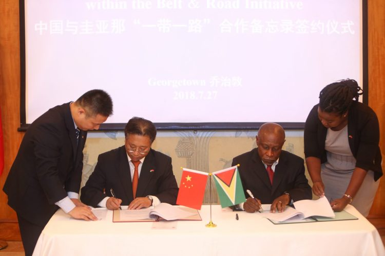 Chinese Ambassador to Guyana, Cui Jianchun and Minister of Foreign Affairs, Carl Greenidge, singing the MOU