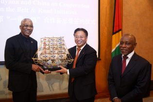 President David Granger receives a representation of the Maritime Silk Road from Ambassador Cui in the presence of Minister Greenidge