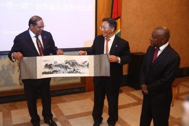 Prime Minister Moses Nagamootoo receives a representation of the Silk Road route from Ambassador Cui in the presence of Minister Greenidge