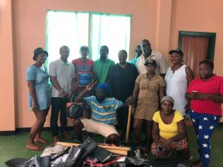 Minister Simona Broomes making donations of farming utensils to the residents