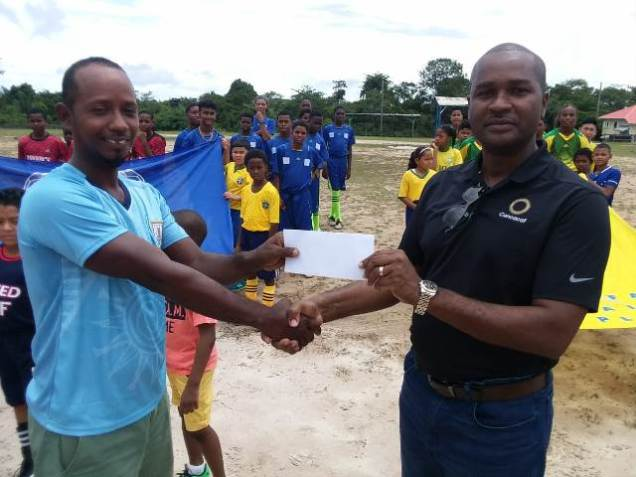 Sherwin Da Silva Collects Second-Place Prize Money on behalf of Lazio FC from GFF President Wayne Forde.