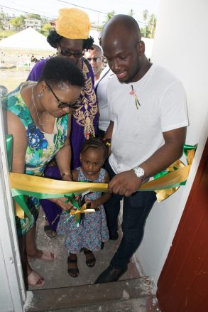 Minister Lawrence and Denroy Tudor assist a little lady to cut the ribbon to officially open the Community Centre