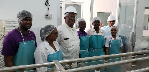 Minister of Finance Winston Jordan takes a moment with some staff working on fruit preparation in the DDL TOPCO Juice Plant