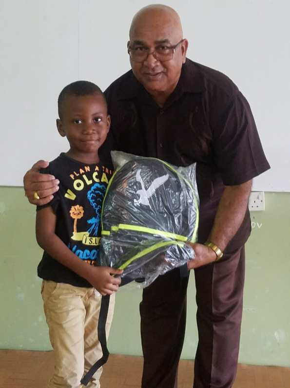 Regional Executive Officer Denis Jaikaran presents a school bag to a student