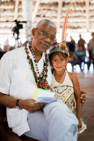 President David Granger shares a light moment with this beautiful little girl while at Heritage Day celebrations at Shulinab Village, Upper Takutu- Upper Essequibo Region.