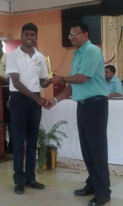 Manager of GuySuco Training Centre Port Mourant (GTC/PM), Jainarine Sookpaul presents a trophy to one of the best-performing students