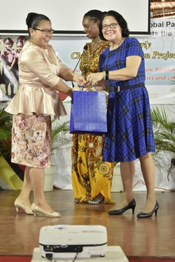 First Lady Mrs. Sandra Granger presenting a token to one of the Master Trainers