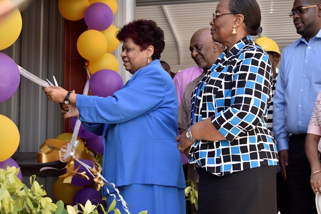 Minister of Social Protection, Ms. Amna Ally cutting the ceremonial ribbon to commission the new elevator, as Junior Minister, Mr. Keith Scott and Permanent Secretary, Ms Lorene Baird and other officials look on.