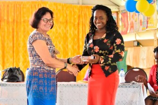 First Lady, Mrs. Sandra Granger presents a token to Mrs. Michelle Campbell-Craig, a teacher of the Lusignan Primary School.