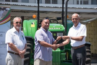 Minister of Communities, Ronald Bulkan hands over the tractor keys to Mayor of Lethem, Kerry Jarvis. Managing Director of GENEQUIP and supplier of the machines, Renger Vandik poses for the picture.