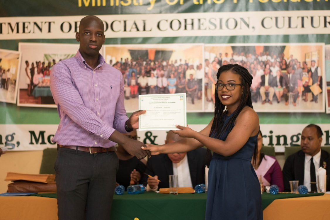 Dr. Rei-launya Amsterdam receiving her certificate from Deputy-Director of Education and Training, Ronald Austin