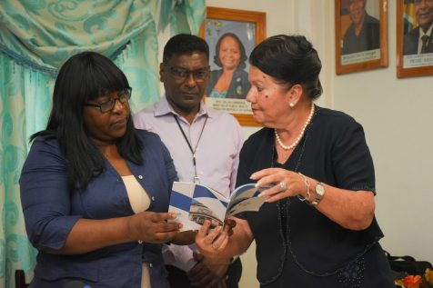 Minister within the Ministry of Public Health, Dr. Karen Cummings and Director of the International Relations Department of the Cuban Chamber of Commerce, Dr. Celia Labora Rodriguez, peruse a FarmaCuba pamphlet. Looking on is Chief Medical Officer (CMO), Dr. Shamdeo Persaud
