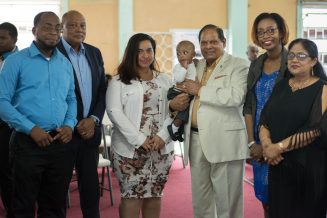 Prime Minister Nagamootoo, his wife and other family members of the Rutherford's stand together at the church alter as the babies are being dedicated