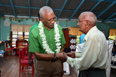 President David Granger interacts with an elderly resident of East Bank Berbice at the conclusion of the community meeting.