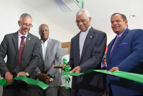President David Granger cuts the ribbon to mark the official opening of GuyTIE as Prime Minister Moses Nagamootoo, Minister of Business, Dominic Gaskin and Minister of State, Joseph Harmon look on.