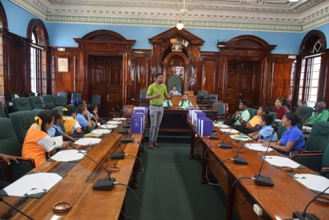 Yannick December explaining to students on the functions of Sitting National Assembly and Parliament of Guyana.