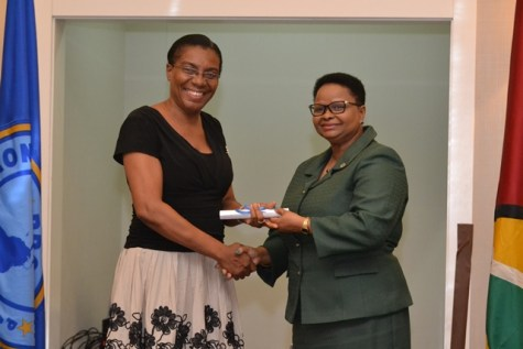 Mandy La Fleur receiving her scholarship award from the Minister of public health, Volda Lawrence.