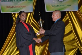 Kimberly Manbodh receiving her award for Best Graduation Student out of the National School of Dance from Minister of Social Cohesion, Dr. George Norton.