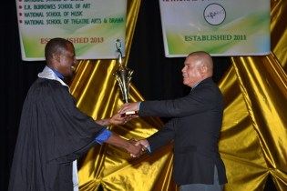 Austin Sindo receiving his award for Best Graduation Student out of the National School of Music from Minister of Social Cohesion, Dr. George Norton.