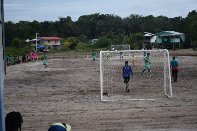 Residents of Karrau enjoy a friendly football game on the newly constructed football field