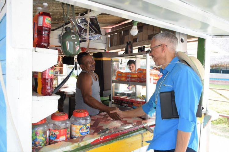 Minister of Business with responsibility for Tourism, Dominic Gaskin interacting with a small business owner in Orealla