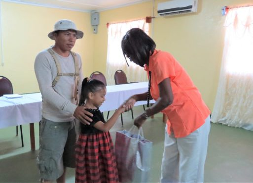 Ms. Wilfred Toney hands over school supplies to one students of Nappi Primary