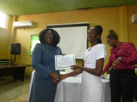 Minister within the Ministry of Public Health, Dr. Karen Cummings presenting one of the graduates with her certificate.