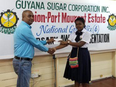 A Representative from the GuySuCo's training centre presenting bursary award to Janaya Jaipersaud