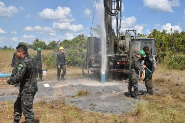 Members of the Brazilian Army's Sixth Battalion Engineering Corps celebrate as water spurts from a well that they dug in Chukrikednau Village