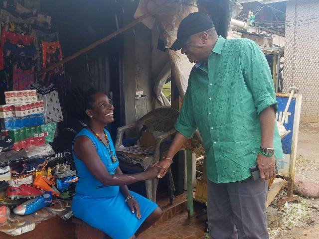 Minister Joseph Harmon greets a resident during a walkabout of the Port Kaituma community.