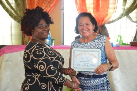 First Lady Mrs. Sandra Granger (right) presents a certificate to Ms. Tiffannee Welcome following her successful completion of the Self-Reliance and Success Workshop.
