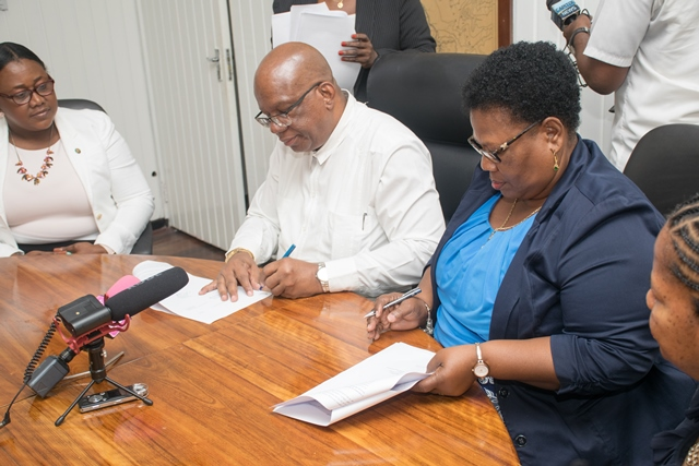 Minister of Finance, Winston Jordan [left] and President of the National Mining Syndicate Inc., Cheryl Williams [right] sign the concessional agreement for small and medium scale miners.