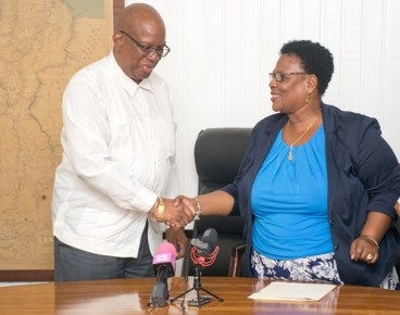 Minister of Finance, Winston Jordan [left] and President of the National Mining Syndicate Inc., Cheryl Williams [right] shake hands after the signing of the concessional agreement for small and medium scale miners.