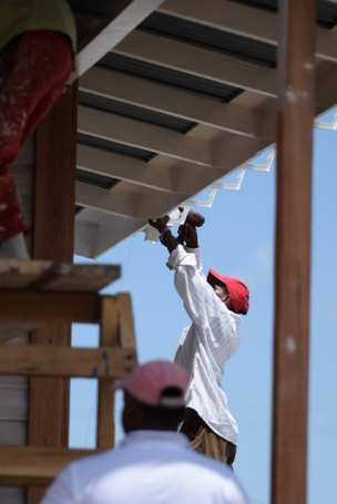 This worker installs the guttering on the CHPA low-income model home.